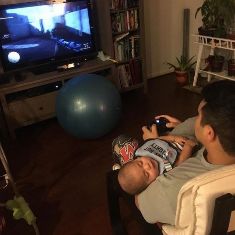 papa met slapend kind in zetel voor tv