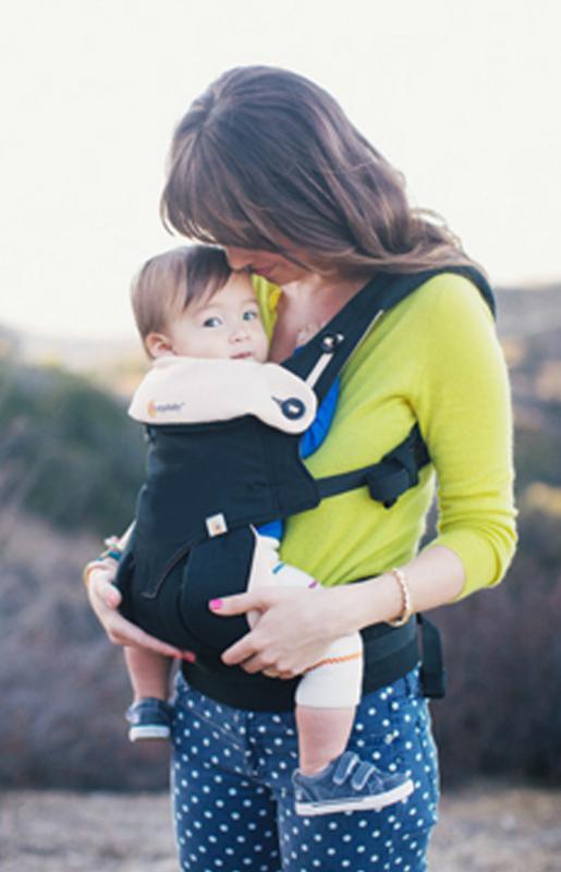 Mama die baby draagt in draagzak