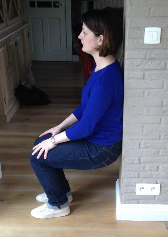 vrouw doet spieroefeningen tegen muur