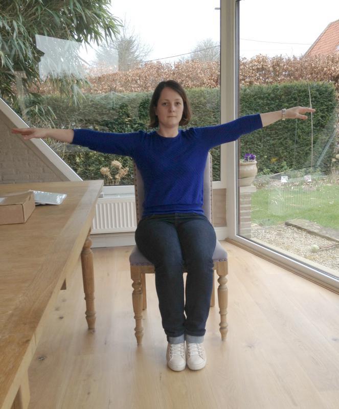 vrouw doet armspieroefening op stoel