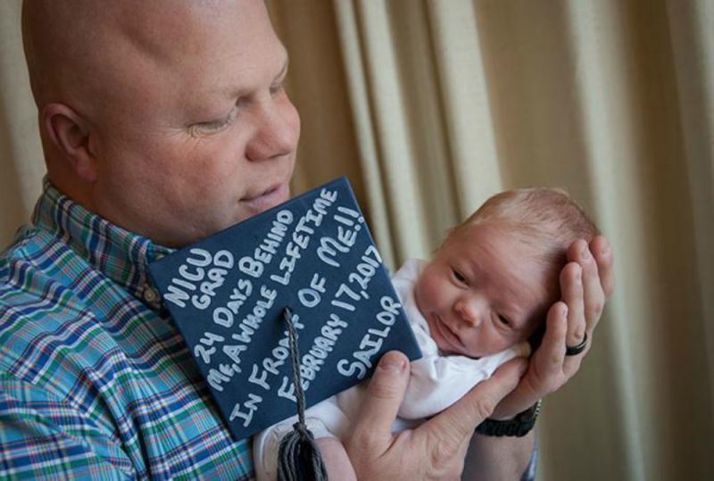 premature baby met afstudeerhoed bij de papa