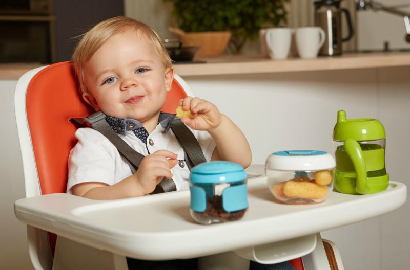 Kindje aan het eten met bordje, doosje en beker in de stoel