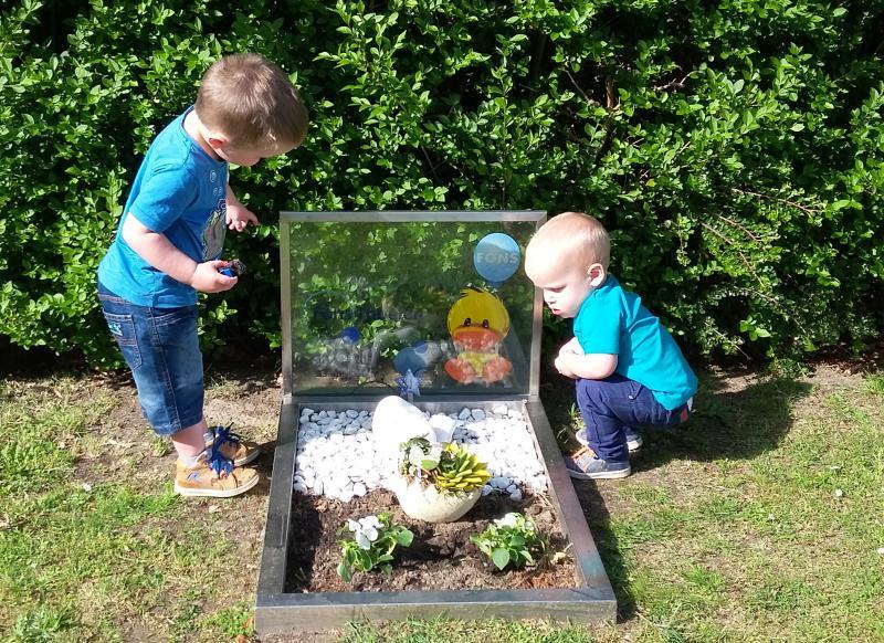twee jongens aan grafje baby