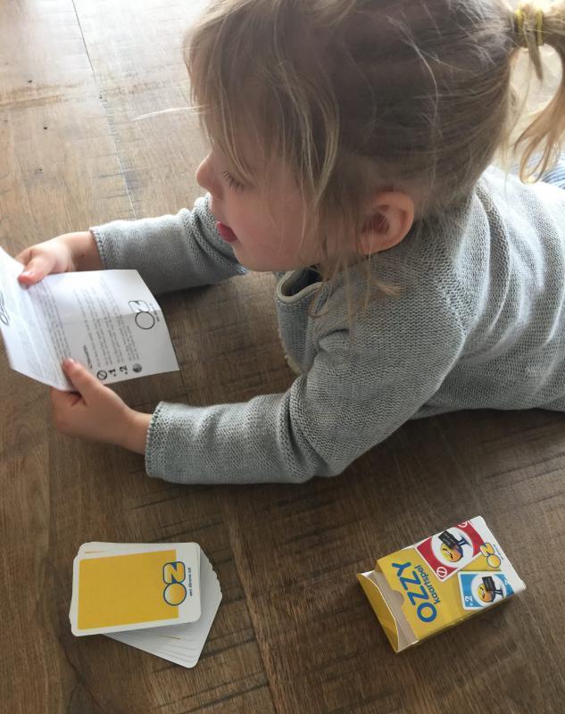 meisje met papier in de hand en kaartspel OZ Ozzy naast haar