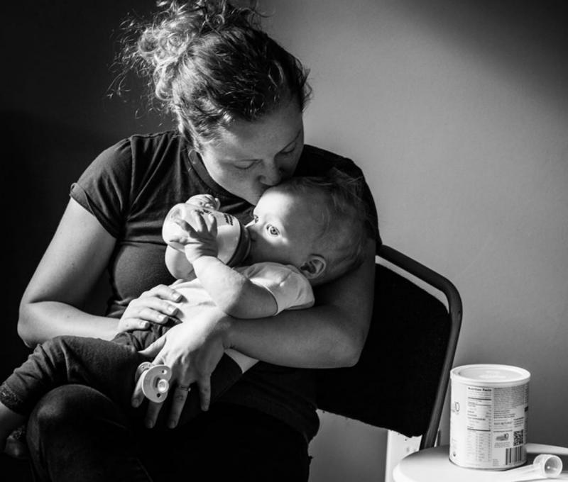 mama geeft flesje aan baby
