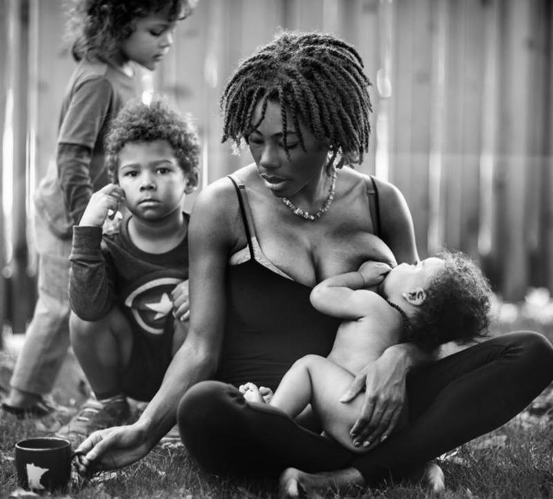 mama geeft borst aan baby, twee kinderen achter haar