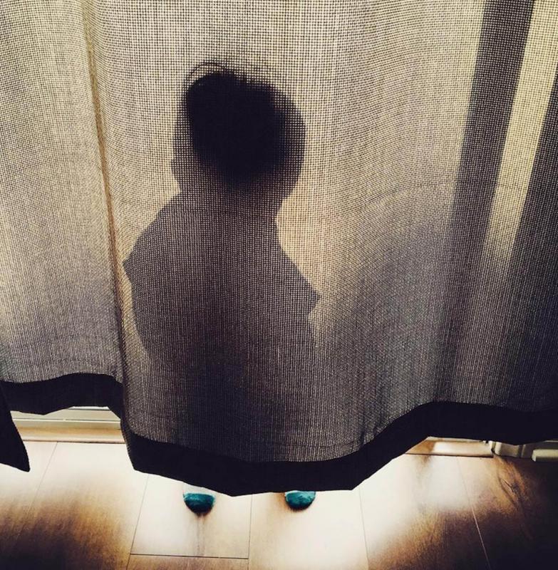 kind verstopt achter gordijn