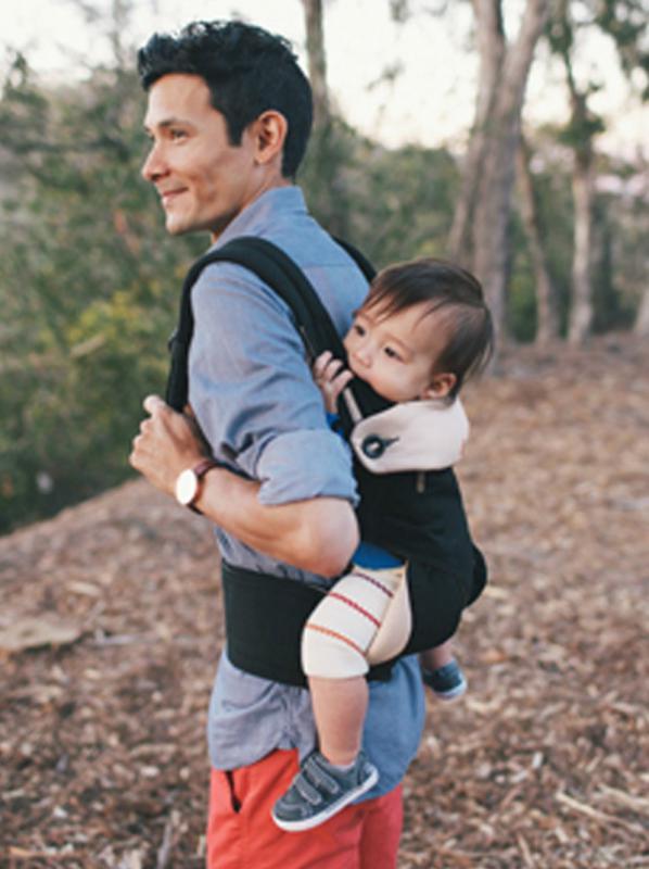 Papa draagt baby op zijn rug
