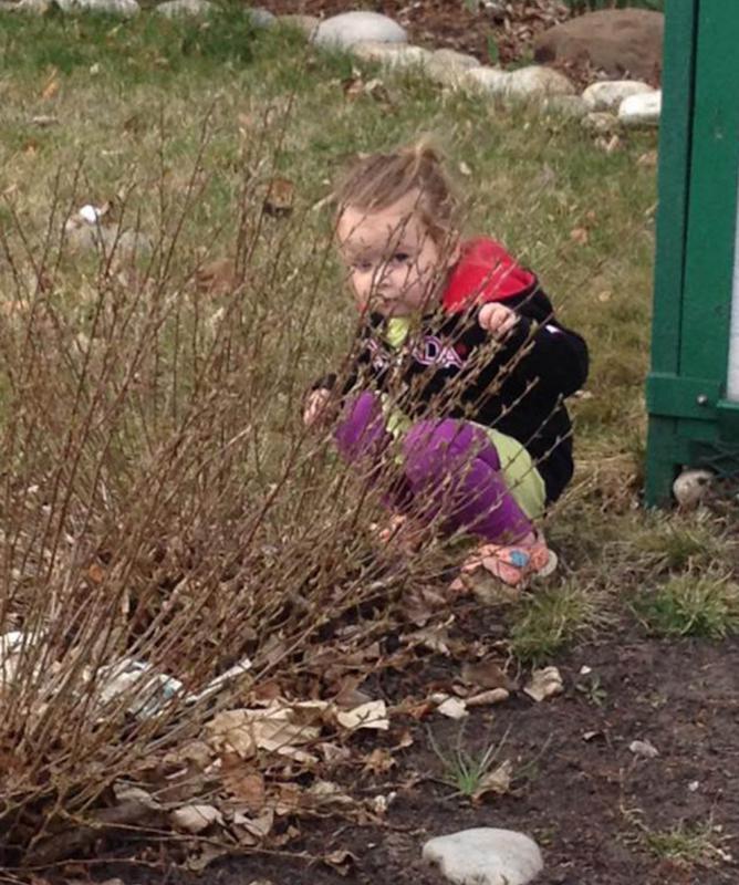 meisje verstopt achter struik