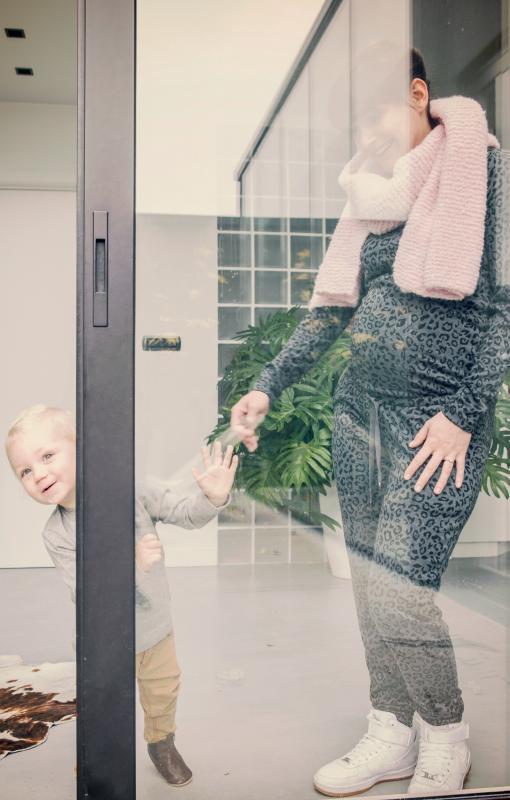 zwangere vrouw aan raam met peuter