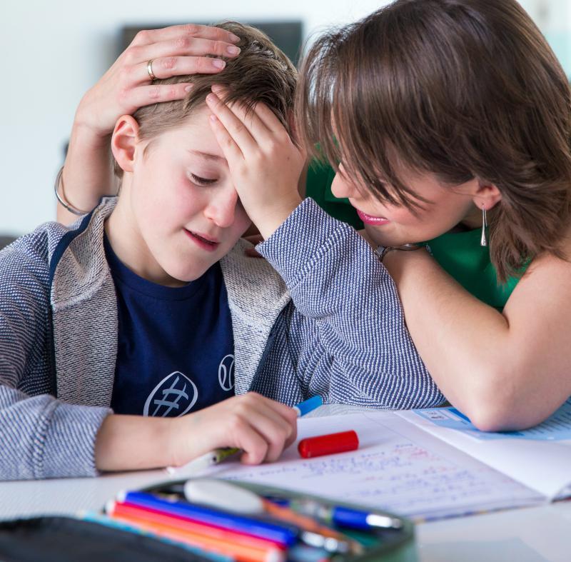 moeder helpt zoon met zijn huiswerk