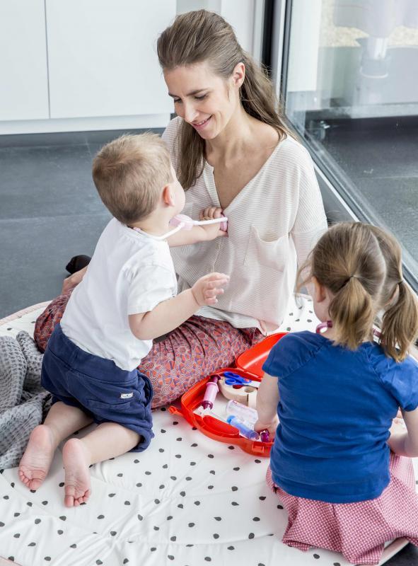 mama met twee kindjes die dokter spelen