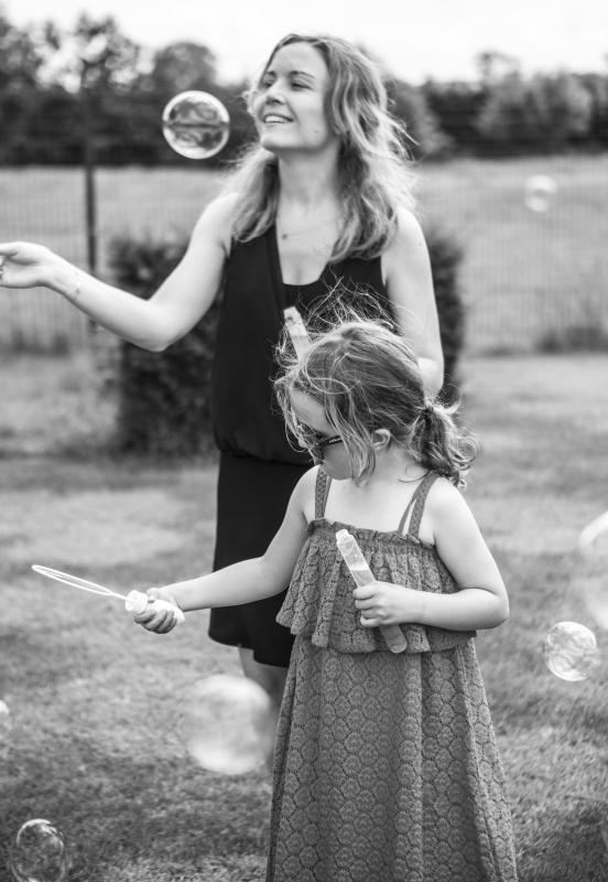mama met dochter blaast belletjes