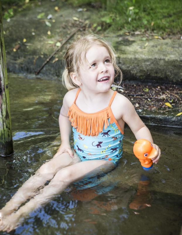 klein meisje met waterpistool in water