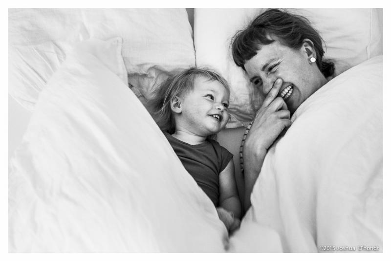 mama en dochter lachend in bed onder de lakens