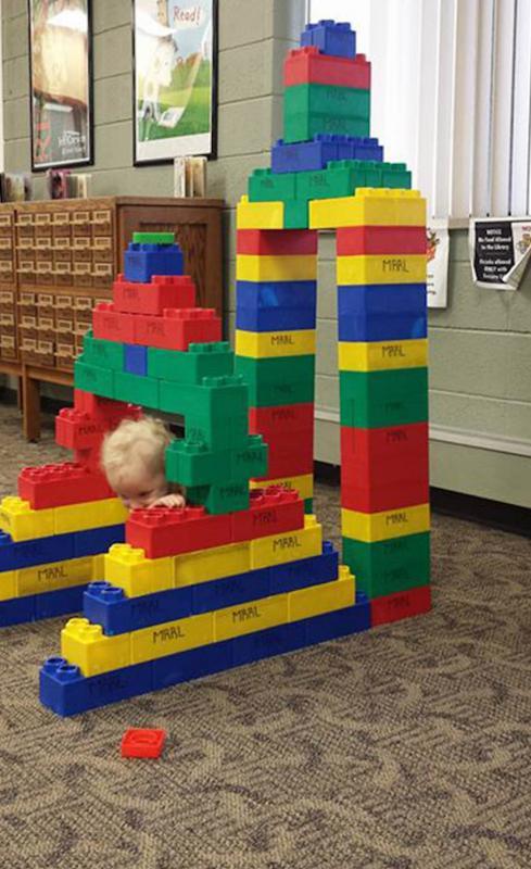 kind verstopt achter lego-toren