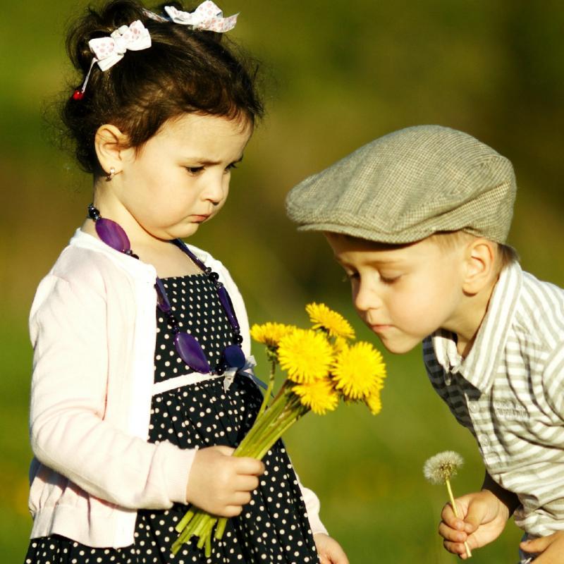 jongen en meisje ruiken aan een bloem