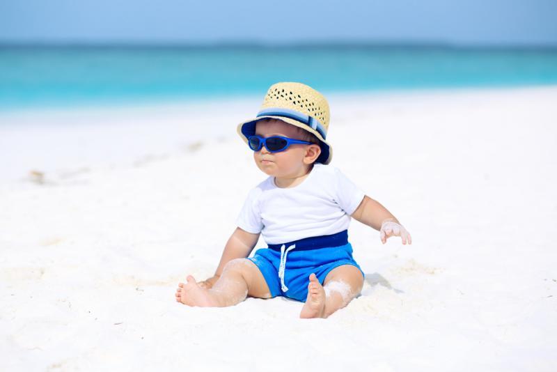 baby jongen op strand met zonnebril en hoed