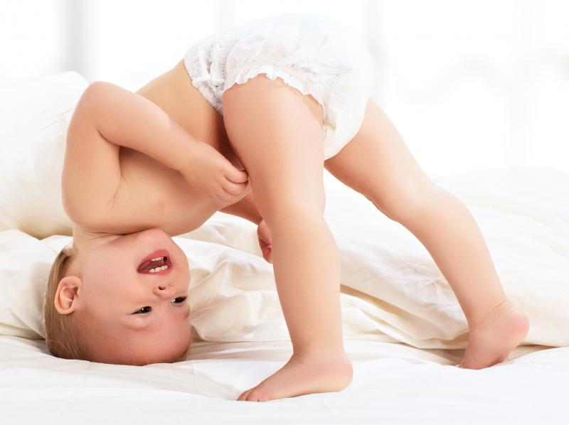 Peuter op hoofd in bed kijkt ondersteboven