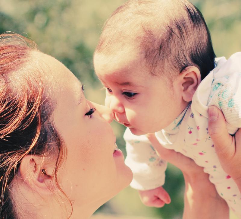 mama geeft kus aan baby