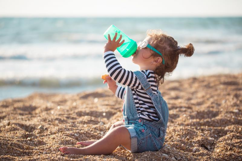 meisje drinkt op strand